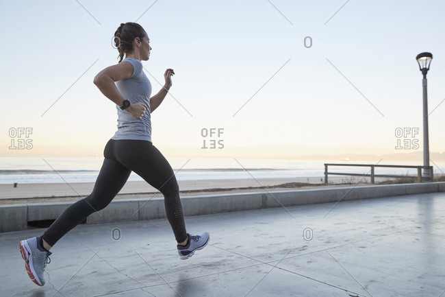Side view of woman jogging against clear sky