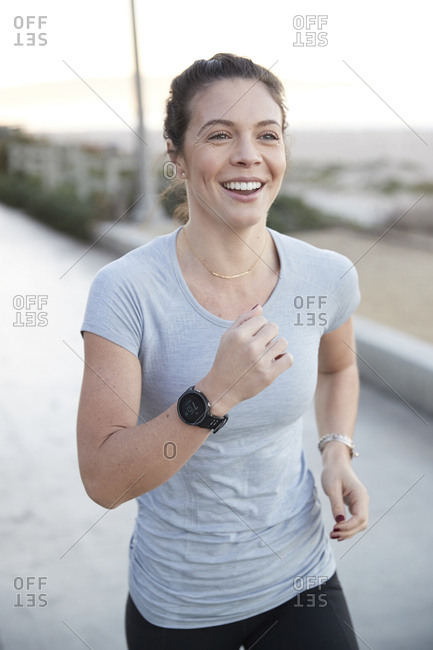 Cheerful woman jogging on footpath