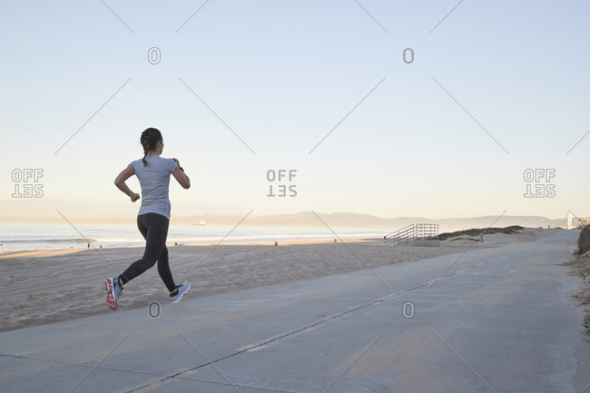 Woman jogging against sea and clear sky