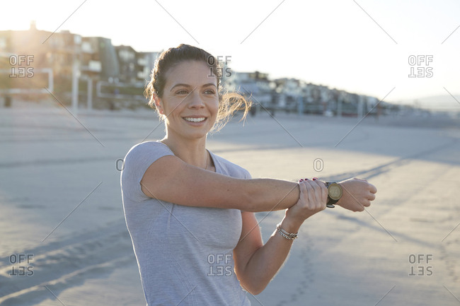 Smiling woman stretching arm during sunny day at beach