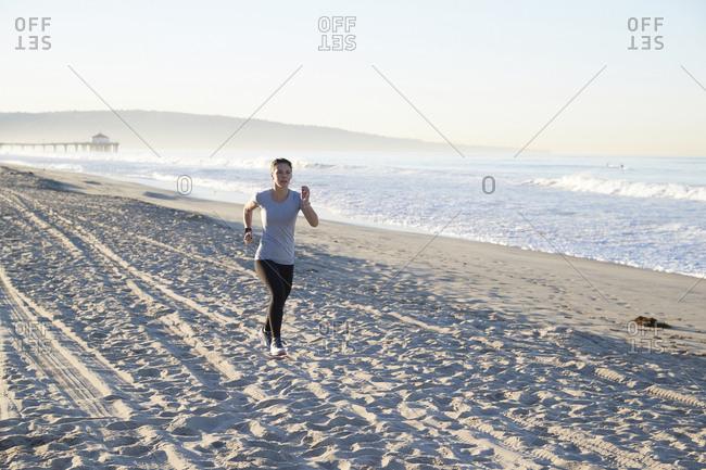 Full length of woman jogging at beach