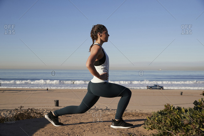 Side view of woman with hands on hip stretching against clear sky at beach