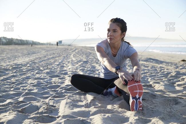 Confident woman stretching leg while exercising at beach