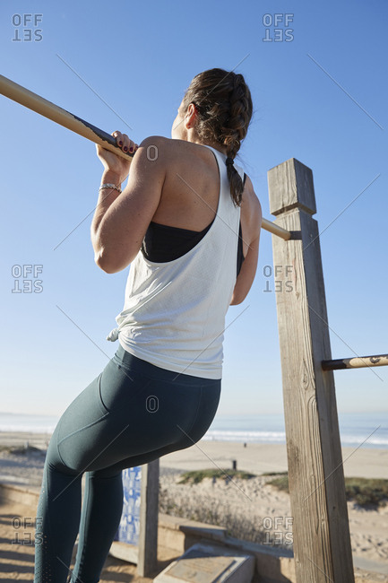 Woman doing chin-ups on gymnastics bar at beach