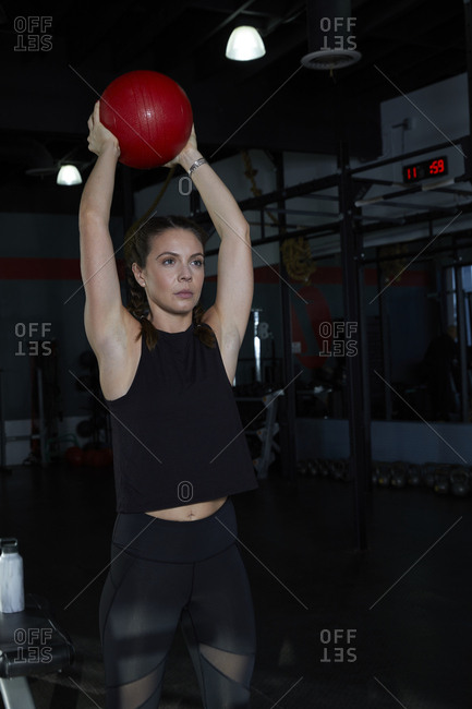 Woman lifting medicine ball while exercising in darkroom of gym
