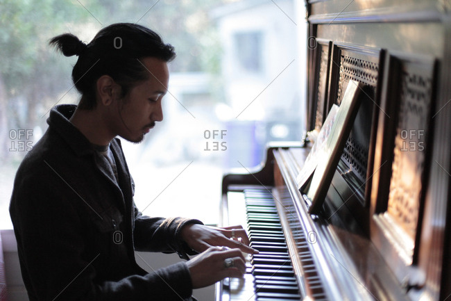 Man playing piano against window at home