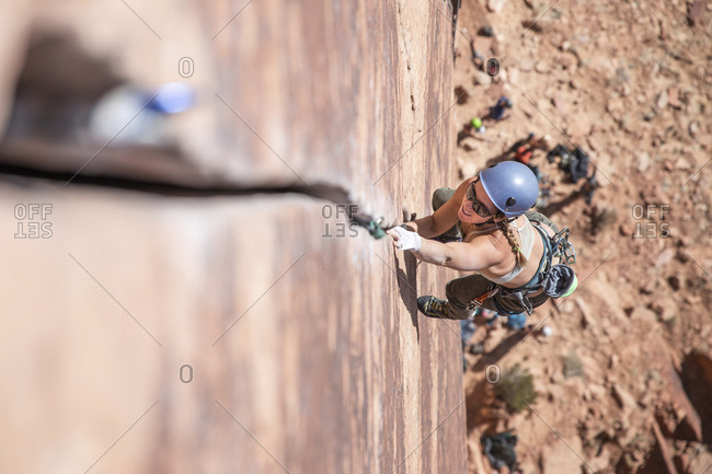 High angle view of female hiker wearing sunglasses while rock climbing