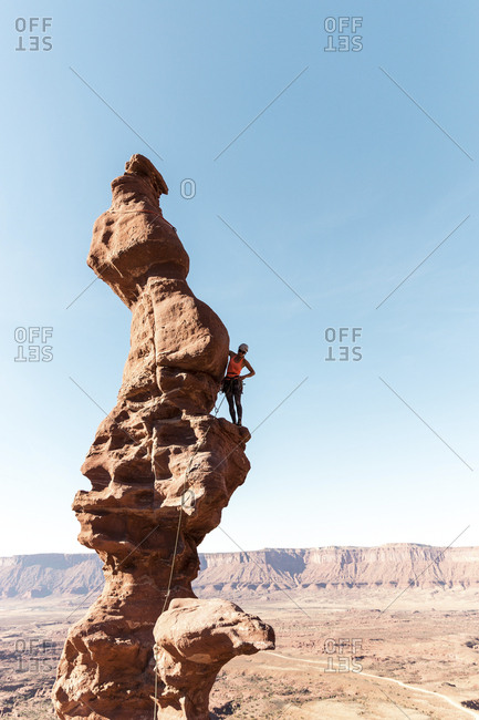 Female hiker standing on rock formation against clear sky during sunny day