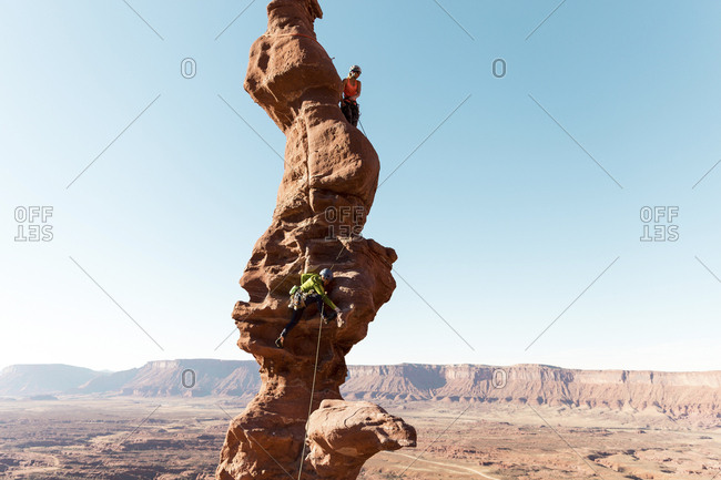 Female hikers climbing on rock formation against clear sky