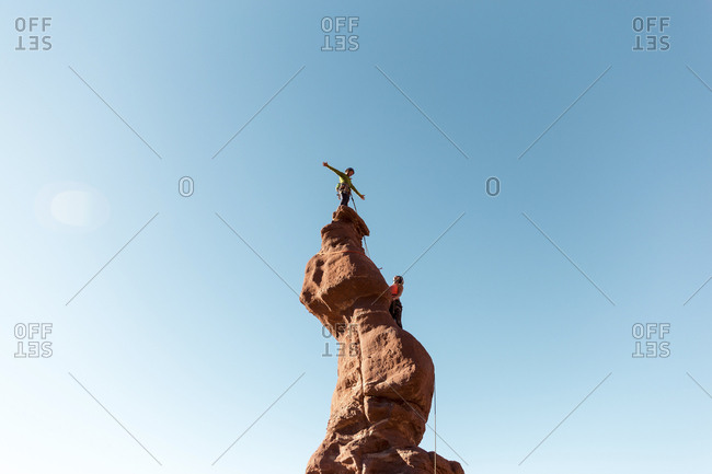 Low angle view of hikers climbing on rock formation against clear sky