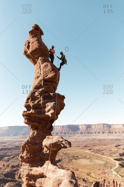 Female hikers with rope climbing on rock formation against clear sky during sunny day