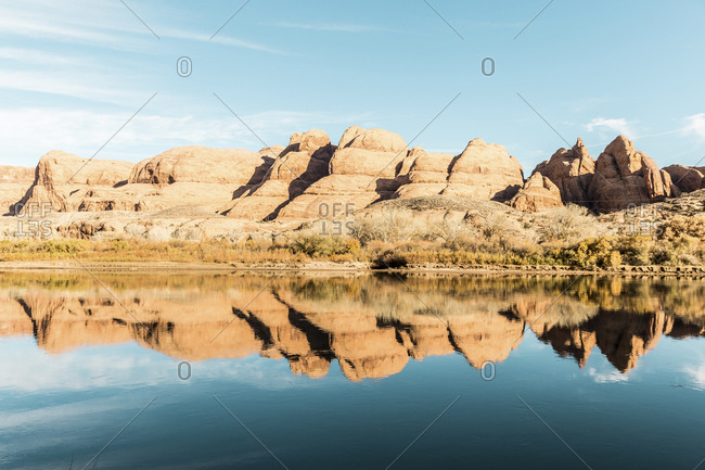 Scenic view of calm lake by mountain against sky