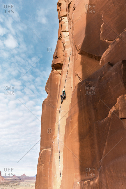 Low angle view of hiker climbing on mountain against sky