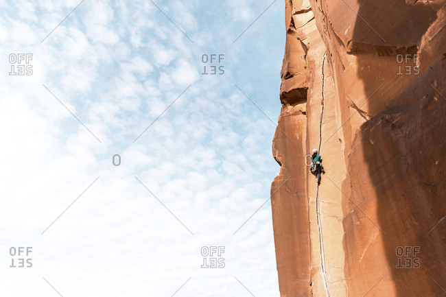 Low angle view of female hiker climbing on mountain against sky