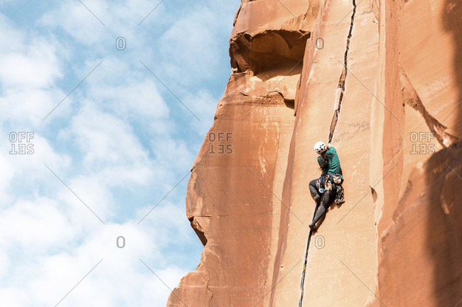 Low angle rear view of hiker climbing on mountain against sky
