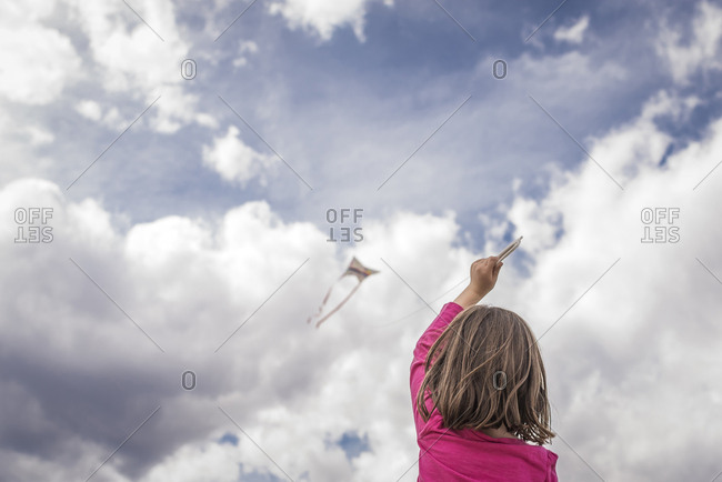 Rear view of girl flying kite against cloudy sky
