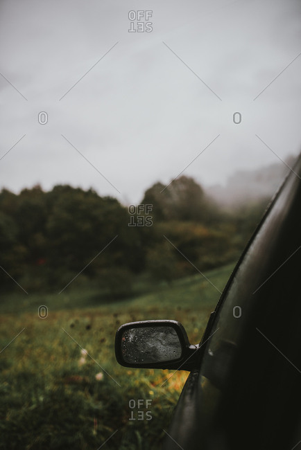 Cropped image of car on field against cloudy sky during rainy season