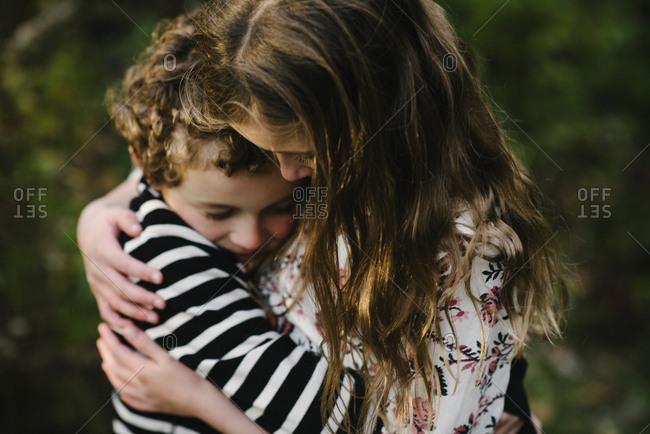 Close-up of loving siblings embracing at park