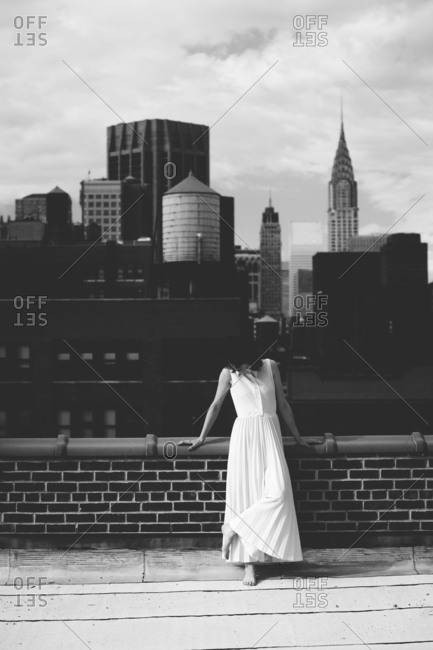 Woman standing on building terrace against cloudy sky in city