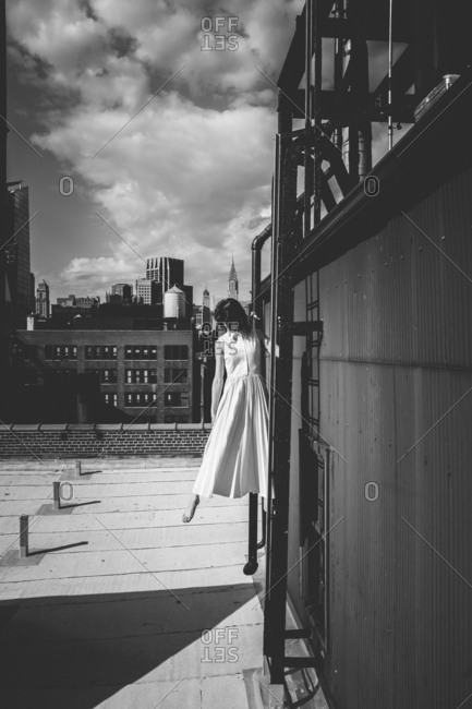 Woman standing on ladder of building terrace against sky in city