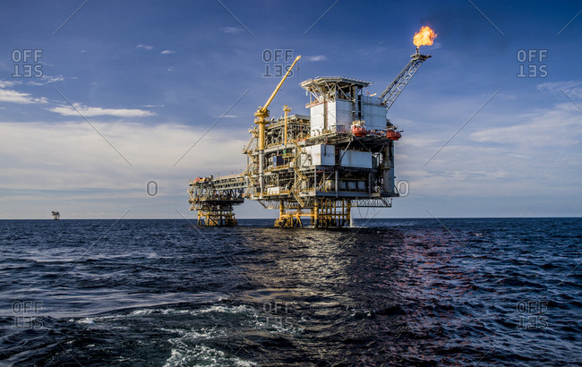 Offshore platform in sea against cloudy sky