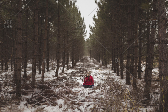 Carefree girl sitting amidst trees at forest during winter