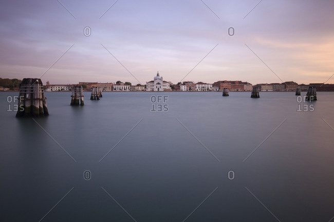 Grand Canal by buildings against cloudy sky during sunset