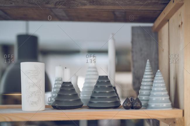 Close-up of potteries on wooden shelf at workshop