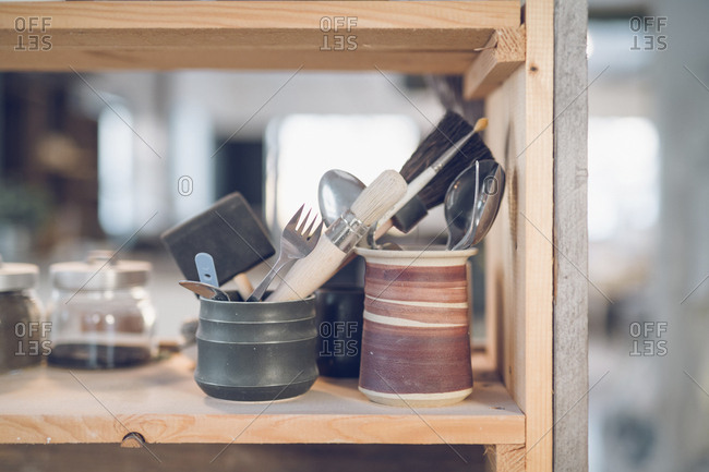 Close-up of cutleries with paintbrushes in containers on shelf at workshop