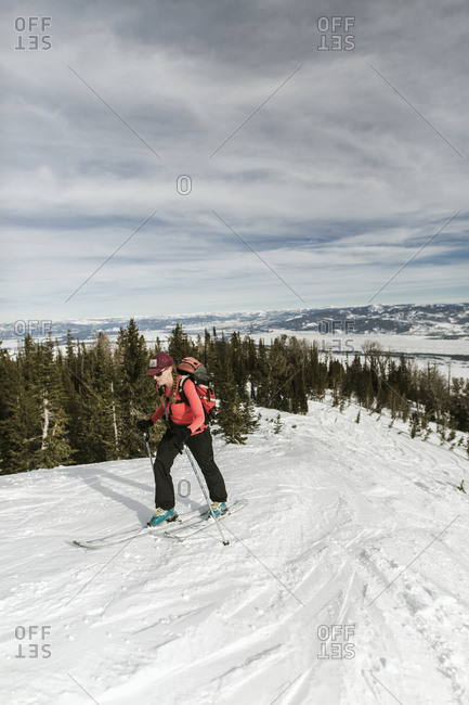 Woman with skies walking on snow covered mountain against cloudy sky at forest