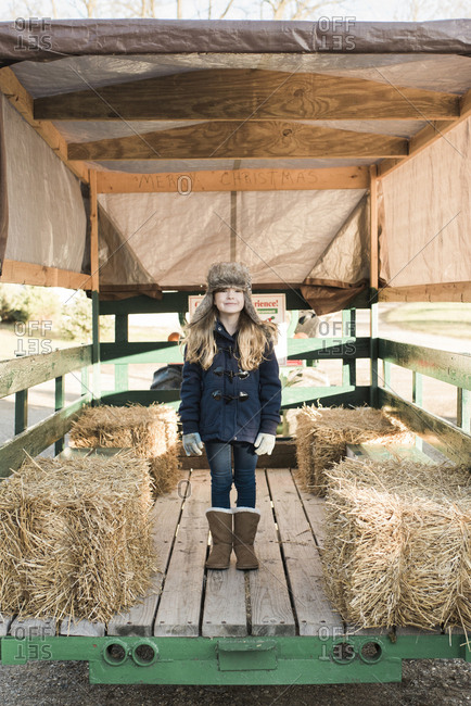 Full length of girl standing on vehicle trailer by hay bales at farm