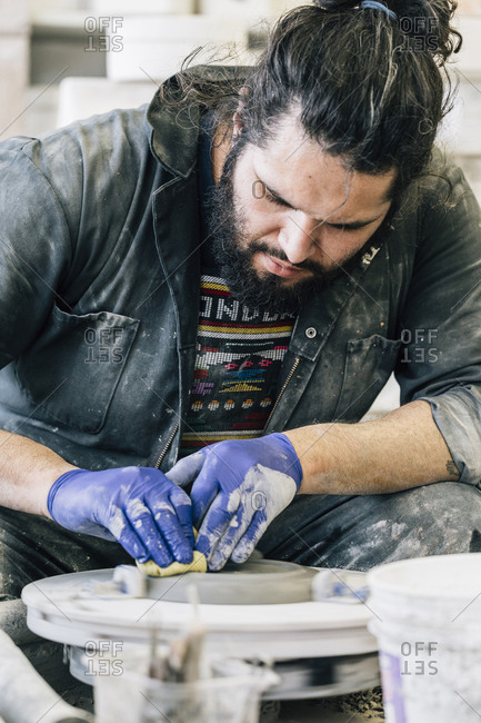 Craftsman cleaning pottery wheel while working in art studio