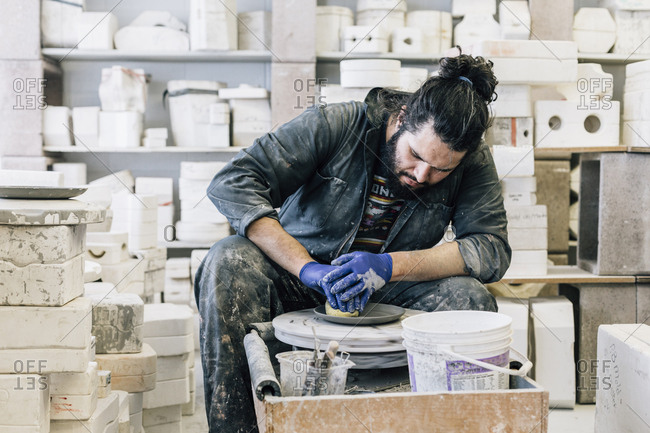 Craftsman using pottery wheel while making earthenware in workshop