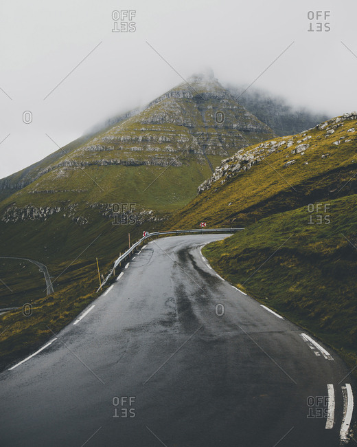 Scenic view of road amidst mountains during foggy weather