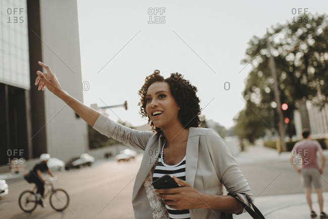Woman hailing while standing on city street against sky