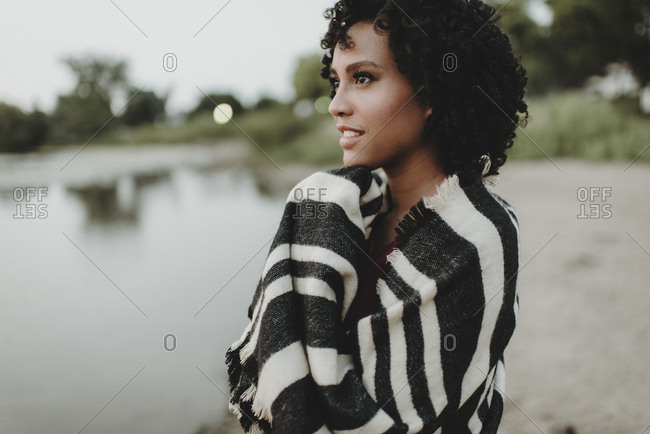 Side view of thoughtful woman wrapped in scarf while looking away on lakeshore