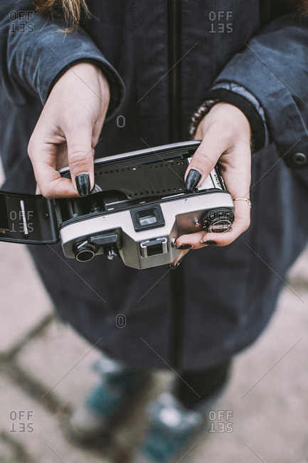 Low section of woman holding vintage camera with film negative while standing on footpath