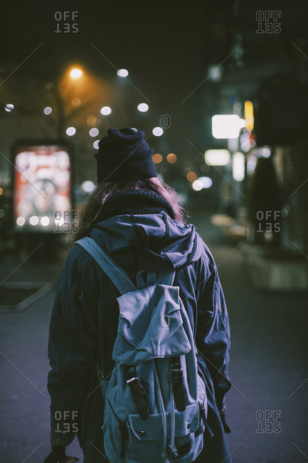 Rear view of woman with backpack standing in city during night