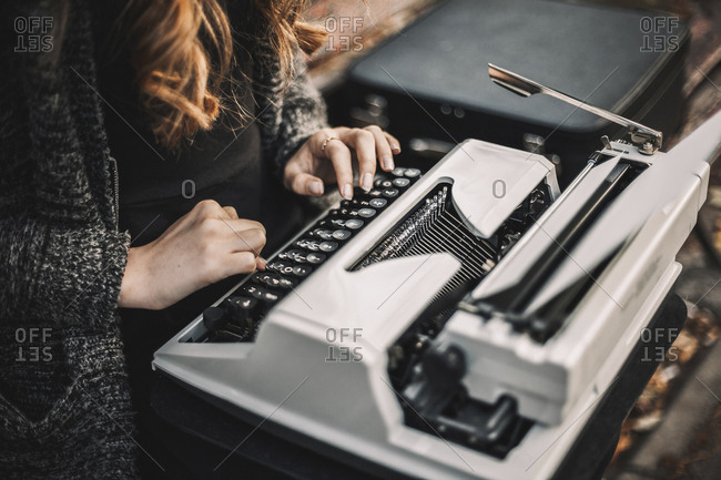 Midsection of female writer using typewriter while sitting on bench at park