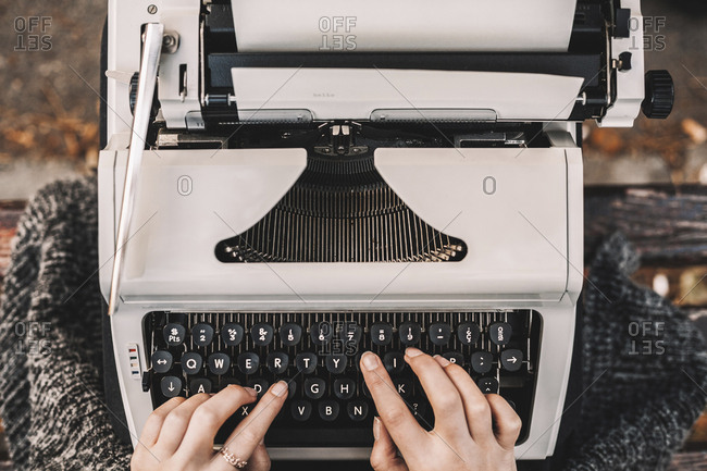 Cropped image of female writer using typewriter while sitting on bench at park