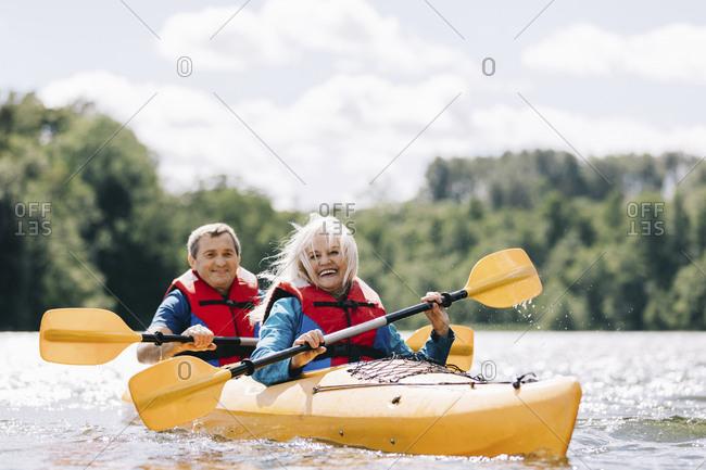 Happy senior couple kayaking on lake against cloudy sky