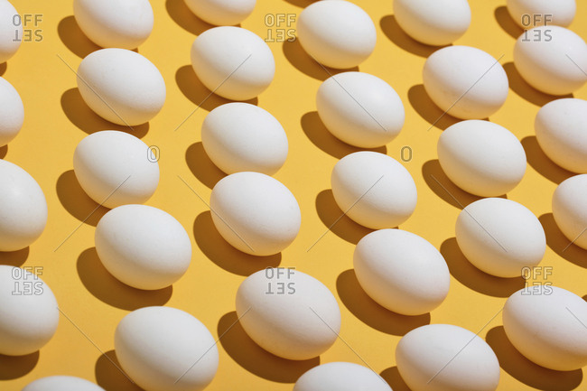High angle view of eggs arranged on yellow background