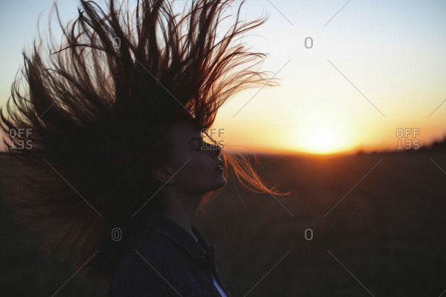 Side view of woman with eyes closed tossing hair while standing against sky during sunset