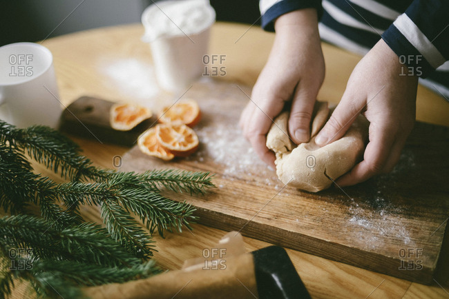 Cropped hands of woman kneading dough on cutting board in kitchen at home