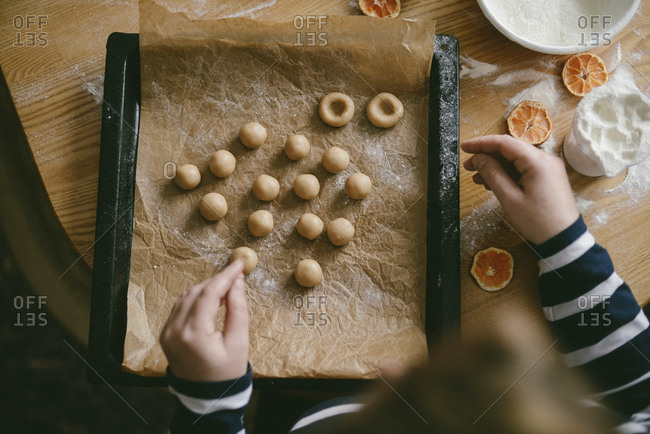 Cropped hands of woman preparing dough balls in baking sheet on table at home