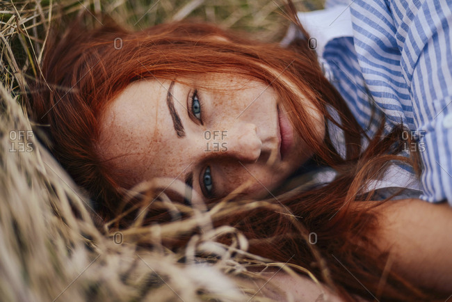 Close-up portrait of teenage girl with red head lying on grassy field