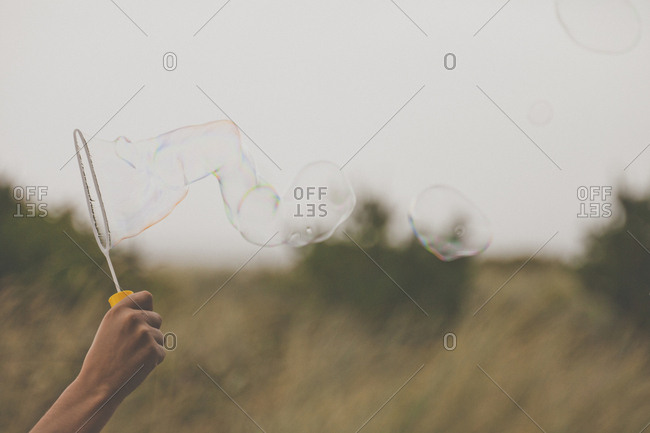 Cropped hand of man holding bubble wand on field
