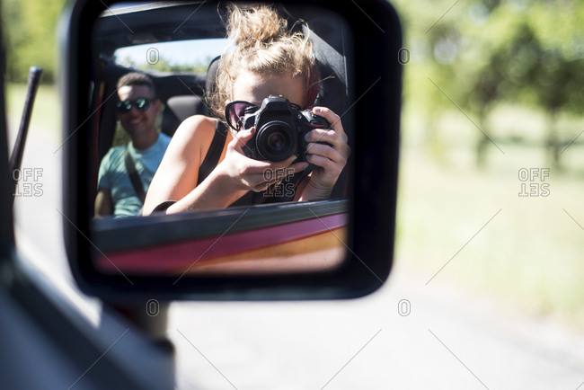Woman photographing reflecting on side-view mirror while traveling with friend in off-road vehicle