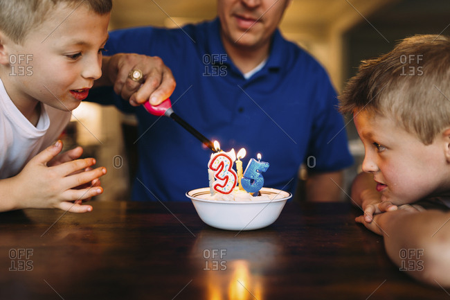 Curious brothers looking at father lighting birthday candles with  lighter on table at home