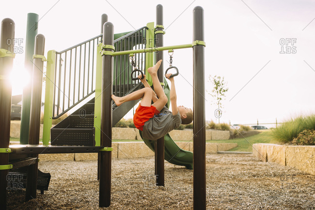 Playful boy hanging on outdoor play equipment while playing at playground